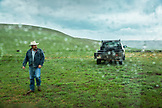 USA, Oregon, Enterprise, Cowboy and Rancher Todd Nash walks in the rain in front of his old pickup truck