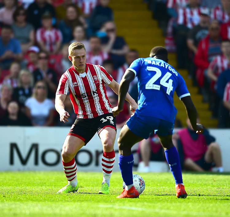 Lincoln City's Danny Rowe vies for possession with Tranmere Rovers' Zoumana Bakayogo<br /> <br /> Photographer Andrew Vaughan/CameraSport<br /> <br /> The EFL Sky Bet League Two - Lincoln City v Tranmere Rovers - Monday 22nd April 2019 - Sincil Bank - Lincoln<br /> <br /> World Copyright © 2019 CameraSport. All rights reserved. 43 Linden Ave. Countesthorpe. Leicester. England. LE8 5PG - Tel: +44 (0) 116 277 4147 - admin@camerasport.com - www.camerasport.com