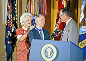 United States President George H.W. Bush, right, and first lady Barbara Bush, left, award the Presidential Medal of Freedom to National Security Advisor Brent Scowcroft, center,  in the East Room of the White House in Washington, DC on July 3, 1991.<br /> Credit: Howard L. Sachs / CNP
