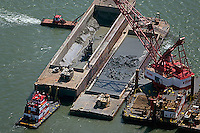 aerial photograph crane depositing dredge material into barges while tug boats hold barges in place Port of Oakland, California