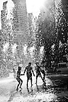Children playing in city splash fountain. Black and white, silhouetted.