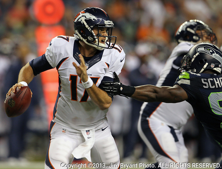 Denver Broncos quarterback Brock Osweiler scrambles past Seattle Seahawks O'Brien Schofield at CenturyLink Field in Seattle, Washington on  August 17, 2013. The Seattle Seahawks beat the Broncos 40-10.     ©2013. Jim Bryant Photo. All Rights Reserved.
