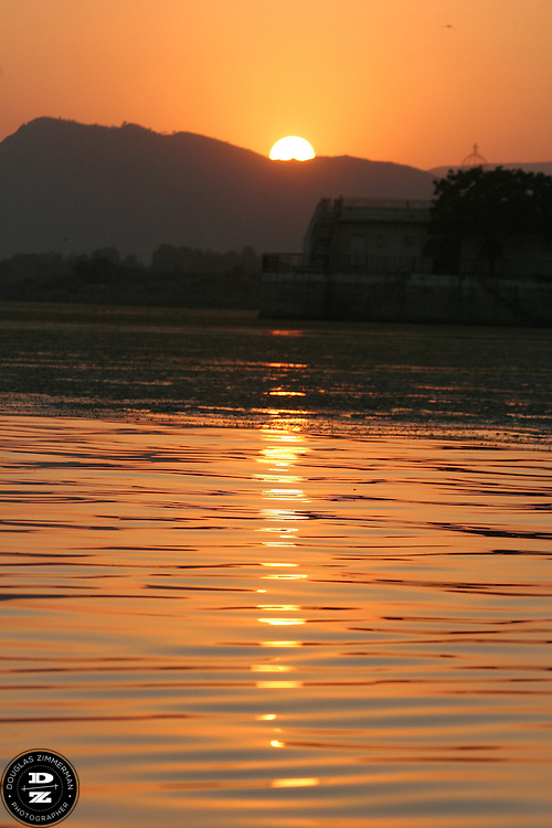 """The sun sets behind the mountain surrounding Pichola Lake, in Udaipur, Rajasthan, India.  Udaipur is located in a valley surrounded by the Aravalli hills, and at its center is the Pichola Lake.  The scenic city has been described as """"the most romantic spot on the continent of India"""" (by Colonel James Tod).  Photograph by Douglas ZImmerman"""
