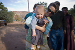 """Aug 9, 2008 -- COLORADO CITY, AZ: A member of the Jessop family, polygamist members of the FLDS, and her child at a picnic at the Jessop home in Colorado City, AZ. Colorado City and neighboring town of Hildale, UT, are home to the Fundamentalist Church of Jesus Christ of Latter Day Saints (FLDS) which split from the mainstream Church of Jesus Christ of Latter Day Saints (Mormons) after the Mormons banned plural marriage (polygamy) in 1890 so that Utah could gain statehood into the United States. The FLDS Prophet (leader), Warren Jeffs, has been convicted in Utah of """"rape as an accomplice"""" for arranging the marriage of teenage girl to her cousin and is currently on trial for similar, those less serious, charges in Arizona. After Texas child protection authorities raided the Yearning for Zion Ranch, (the FLDS compound in Eldorado, TX) many members of the FLDS community in Colorado City/Hildale fear either Arizona or Utah authorities could raid their homes in the same way. Older members of the community still remember the Short Creek Raid of 1953 when Arizona authorities using National Guard troops, raided the community, arresting the men and placing women and children in """"protective"""" custody. After two years in foster care, the women and children returned to their homes. After the raid, the FLDS Church eliminated any connection to the """"Short Creek raid"""" by renaming their town Colorado City in Arizona and Hildale in Utah. A member of the Jessop family weeds the community corn plot in Colorado City, AZ. The Jessops are a polygamous family and members of the FLDS. Photo by Jack Kurtz / ZUMA Press"""
