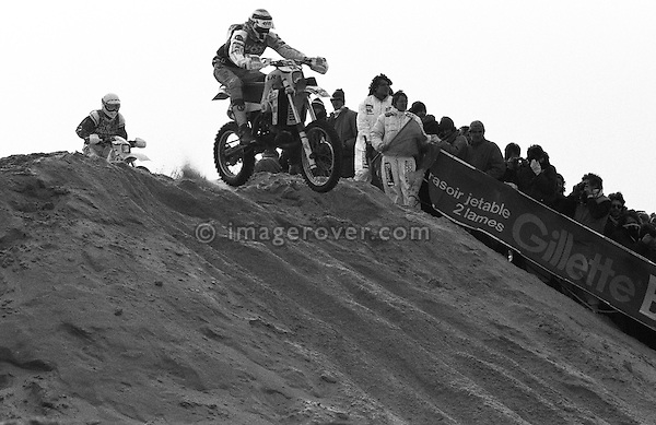 Enduro du Touquet 1986. Dirt bike beach race at Le Touquet, Normandy, France. --- No releases available, but releases may not be necessary for certain uses. Automotive trademarks are the property of the trademark holder, authorization may be needed for some uses. --- Info: A thousand motorcycles take part in this mad event. The race starts along the beach, followed by a run into the sand dunes. The entry point in the dunes is most spectacular: All motorbikes have to pass through a small opening in the dunes. Once the fast professional drivers have flown through, this first passage developes into a true bottleneck with many hundreds of motorbikers trying to get through at the same time. Motorcycles are strewn all over the place. Many have fallen, others have already broken down. In the meantime, the professional riders are progressing quickly. But their riding style changes from racing full-out as soon as they are approaching the lappers from behind. Outmaneuvering them at high speeds is an art form! After three hours it's all over.