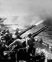 Task Force 58 raid on Japan.  40mm guns firing aboard USS HORNET on 16 February 1945, as the carrier's planes were raiding Tokyo.  Note expended shells and ready-service ammunition at right.  February 1945.  Lt. Comdr.  Charles Kerlee.  (Navy)<br /> NARA FILE #:  080-G-413915<br /> WAR & CONFLICT BOOK #:  1239