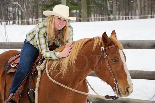 Pretty blonde woman sharing affection and company with with her favorite horse in winter, twenty-something young causcasian female in casual western dress with cowboy hat and flannel shirt, Pennsylvania, PA, USA.