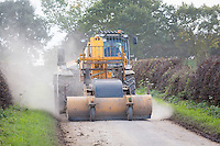 Clearing mud on raod with aroad brush attached to a JCB - Lincolnshire, October