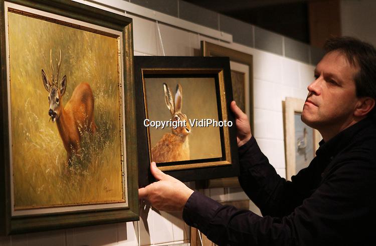 Foto: VidiPhoto..OPHEUSDEN - In de enige wildlife kunstgalerie van Nederland, Oog voor Natuur in Opheusden, wordt donderdag hard gewerkt aan de jubileumexpositie die zaterdag start en duurt tot en met 22 december. De twintig beste natuurschilders en natuurkunstenaars van Europa nemen daaraan deel. Oog voor Natuur staat internationaal hoog aangeschreven. Kunstenaars uit de hele wereld benaderen de Betuwse galerie zelf om daar te mogen exposeren. Zo heeft Oog voor Natuur ook de grootste collectie aan wildlife-artboeken van Europa. Vanwege het tienjarig jubileum van de kunstgalerie worden de komende weken diverse workshops van bekende wildlife-schilders georganiseerd in Opheusden. Wildlife-art neemt in populariteit enorm toe onder Nederlandse kunstverzamelaars. Foto: Eigenaar Wim Smith bezig met het inrichten van de expositie..