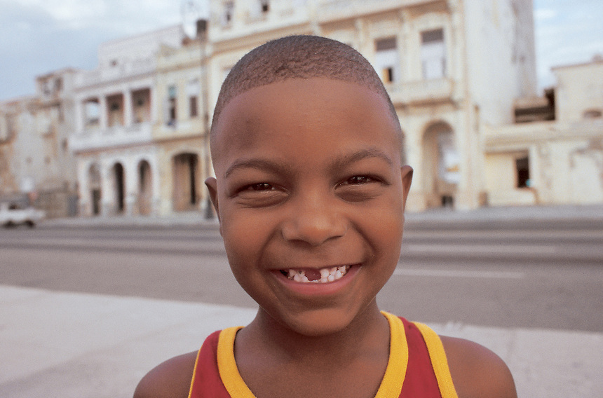 A boy without his front teeth smiles at the camera at Havana's Malecon. Street scenes from Havana, Cuba 9-02