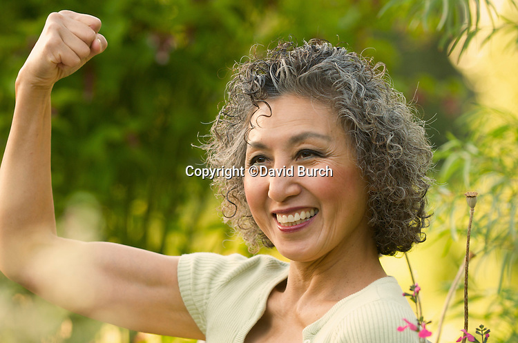 Asian woman flexing her muscles and smiling