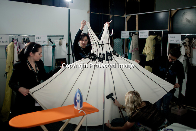 CAPE TOWN, SOUTH AFRICA - JULY 26: Staff prepare a dress backstage before a fashion show with the designer label Gavin Rajah at the Mercedes Benz Cape Town Fashion Week on July 26, 2012, in Cape Town, South Africa. Some of South Africa's finest designers showed their 2012-13 spring and summer collections during the 4-day event. (Photo by Per-Anders Pettersson)