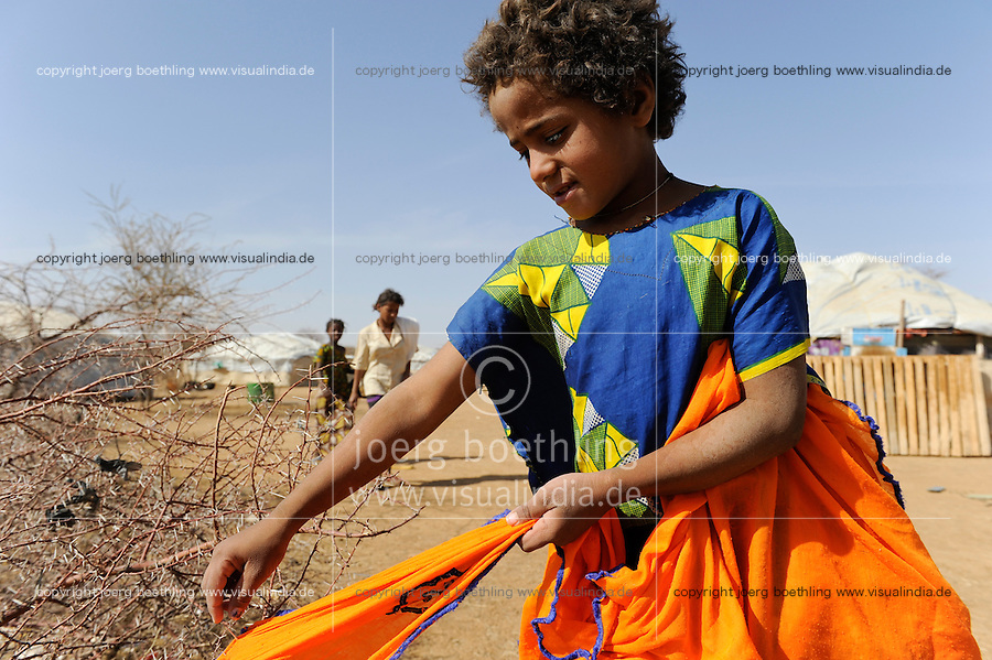 BURKINA FASO Dori , malische Fluechtlinge, vorwiegend Tuaregs, im Fluechtlingslager Goudebo des UN Hilfswerks UNHCR, sie sind vor dem Krieg und islamistischem Terror aus ihrer Heimat in Nordmali geflohen, Maedchen trocknet Waesche im Dorengestruepp / BURKINA FASO Dori, malian refugees, mostly Touaregs, in refugee camp Goudebo of UNHCR, they fled due to war and islamist terror in Northern Mali, girl dry clothes in thorn shrub