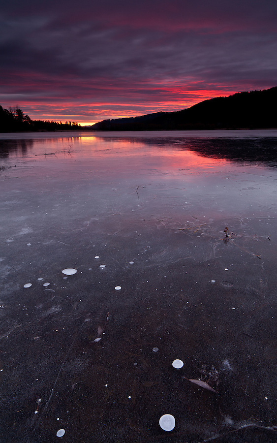 The sun rises as seen from a frozen pond, near Blanchard, Idaho