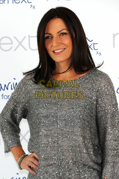 Davina McCall.Photocall to launch new collection for Next, 1 Marylebone, London, England..December 6th, 2011.half length  grey gray silver top  hand on hip.CAP/CJ.©Chris Joseph/Capital Pictures.