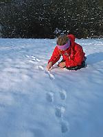Mädchen, Kind zeigt auf Spur, Spurensuche, Feldhase, Feld-Hase, Hase, Trittsiegel, Spur, Pfotenabdrücke im Schnee, Lepus europaeus, Lepus capensis, Brown hare, Lièvre brun