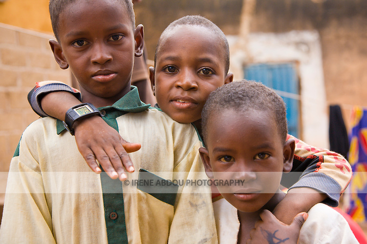 Three brothers from the traditionally pastoralist Fulani ethnic group playfully pose for the camera in Ouagadougou, Burkina Faso.