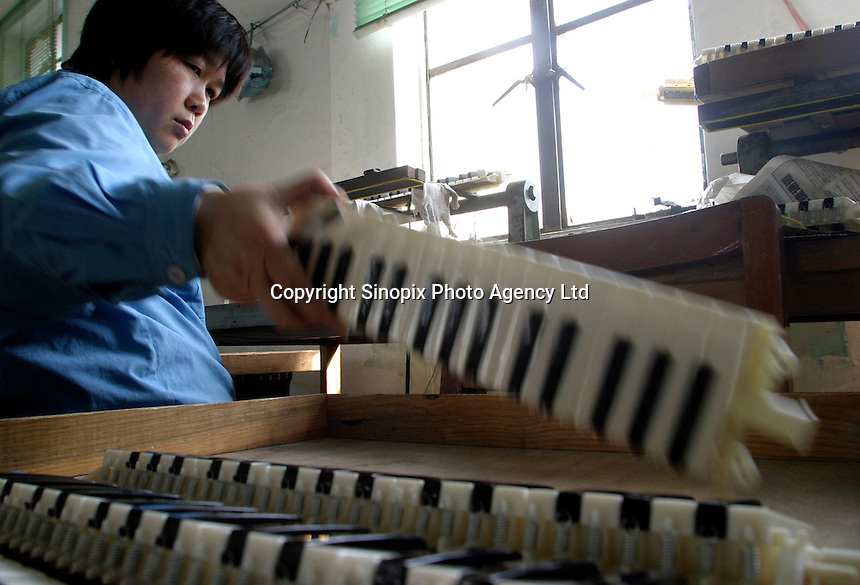 A worker assembles vertical flutes at the Shanghai General Harmonica Factory (SGHF) in Shanghai, China. Although it makes well-respected brands such as the Huang, Suzuki, and Hohner harmonicas that are favored by many professional musicians around the world, the 60 years old state owned SGHF had to trim down its work force from 800 in the mid 1980's to just over 100 today..23-FEB-04