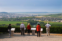 Five people in red white and black standing at a view spot overlooking the Vallee de la Marne, the river and the vineyards with Epernay in the distance, the village of Hautvillers in Vallee de la Marne, Champagne, Marne, Ardennes, France