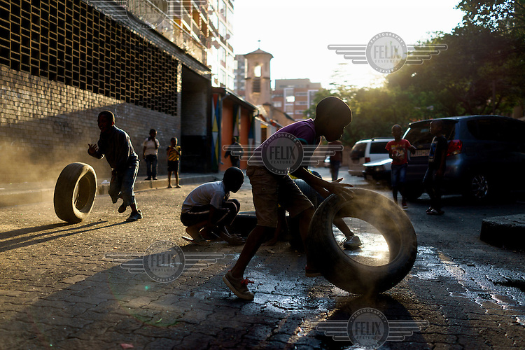 Children play with old car tyres on a quiet street in Hillbrow, an inner-city neighbourhood with a reputation for drugs, violence and crime. The children fill the tyres with gravel and sand, which makes a noise and produces 'engine smoke' as the children roll them along the streets.