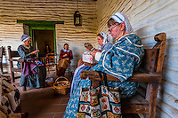 Women of the Old Town San Diego Historic Quilt Guild, demonstrating the process of making quilts. They are wearing Civil War era work dresses (1860's costume), Casa de Estudillo, Old Town, San Diego, California USA.