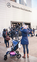 A woman with a baby in a stroller photographs outside of the Fall 2014 Fashion Week shows in Lincoln Center in New York on Saturday, February 8, 2014. This year some designers are abandoning the tents at Lincoln Center to hold their shows at far flung venues, including Brooklyn.  (© Richard B. Levine)