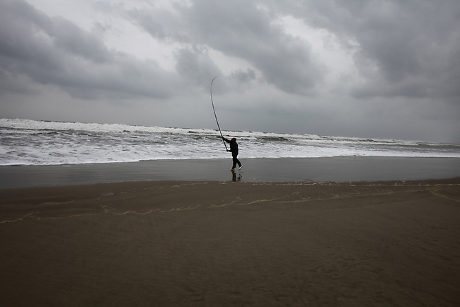 A fisherman casts a line into the surf on a stormy winter day in Da Nang, Vietnam. Dec. 23, 2012.