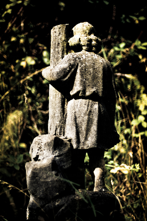 Statue of a young boy in cemetery.