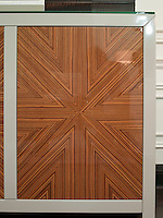 The doors of the sideboard along one wall of the living room are clad in a warm veneer