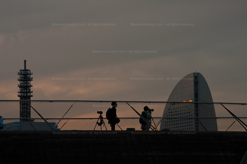 Photographers with tripods photographing the sunset over the Grand Inter-Continental hotel in Yokohama from Osanbashi Pier, Kanagawa, Japan. Saturday October 23rd 2010