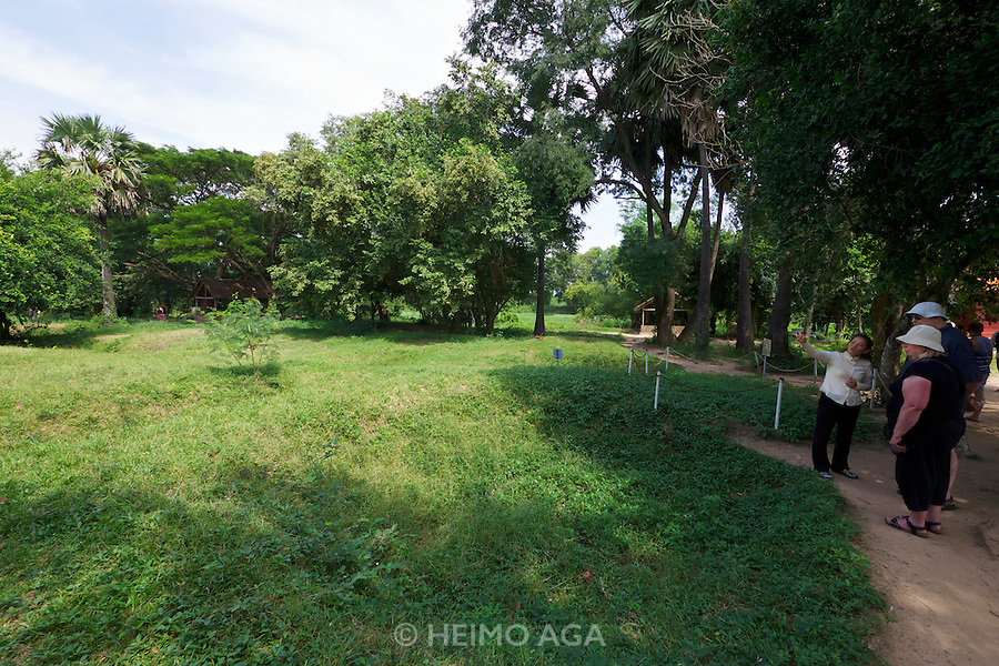 Phnom Penh, Cambodia. Choeung Ek Killing Fields memorial site, a reminder of the genocide committed by the Khmer Rouge.<br /> Tourist stopping at a mass grave during a guided tour.
