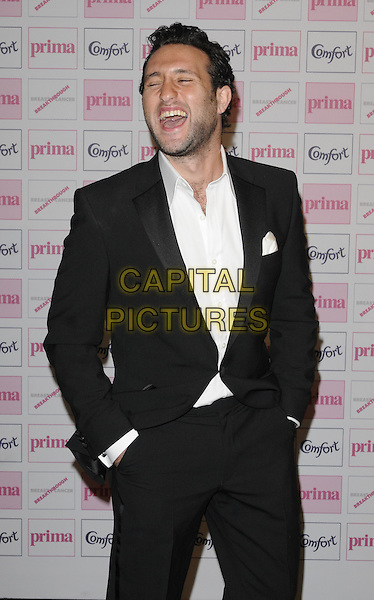 ANTONY COSTA .Comfort Prima High Street Fashion Awards 2010 at Battersea Evolution, London, England, September 9th 2010 half length black suit white shirt beard facial hair hands in pockets funny mouth open laughing eyes shut .CAP/CAN.©Can Nguyen/Capital Pictures.