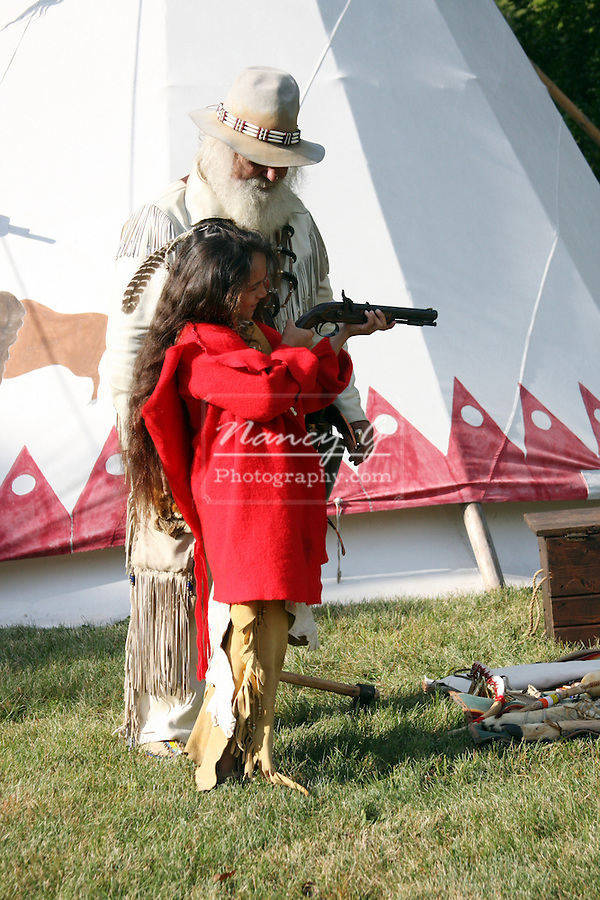 A Native American Indian boy learning how to shoot a gun