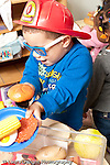 Education preschool 3-4 year olds pretend play in kitchen area boy in dressup fire hat and glasses playing with toy plastic food vertical