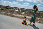 Milka on a walk along with her son riding a toy car, at the unauthorized Israeli settler-outpost of Chavat Gilad, West Bank.