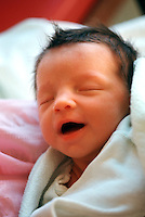 Portrait of the face of a 'smiling' newborn baby.