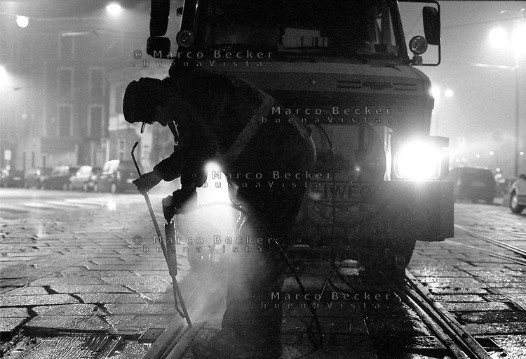 milano, zona navigli. un operaio addetto alla manutenzione delle rotaie del tram al lavoro --- milan, navigli channels area. a maintenance worker of tram rails