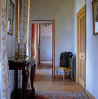 One of several corridors which connect the various bedrooms has marbleised walls and simple curtains