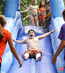 SOUTHBURY, CT - 08 July 2004 - 070804BZ01- Andrew Bleidner, 11, of Southbury, slides down the &quot;Aqua Tunnel&quot;, an inflatable water slide, while camp counselors Erika Jannetty, 18 , of Southbury, (left) and Andrea Northup, 17, of Southbury, prepare to catch him during a Southbury Parks and Recreation summer camp outing at  Ballantine Park in Southbury Thursday morning.  The parks and recreation department holds a kindergarten through 5th grade summer camp from the end of June through August.  The camp is run in 3 2-week long sessions from 7:30 a.m. to 5 p.m. Monday through Thursday. <br /> Jamison C. Bazinet Photo