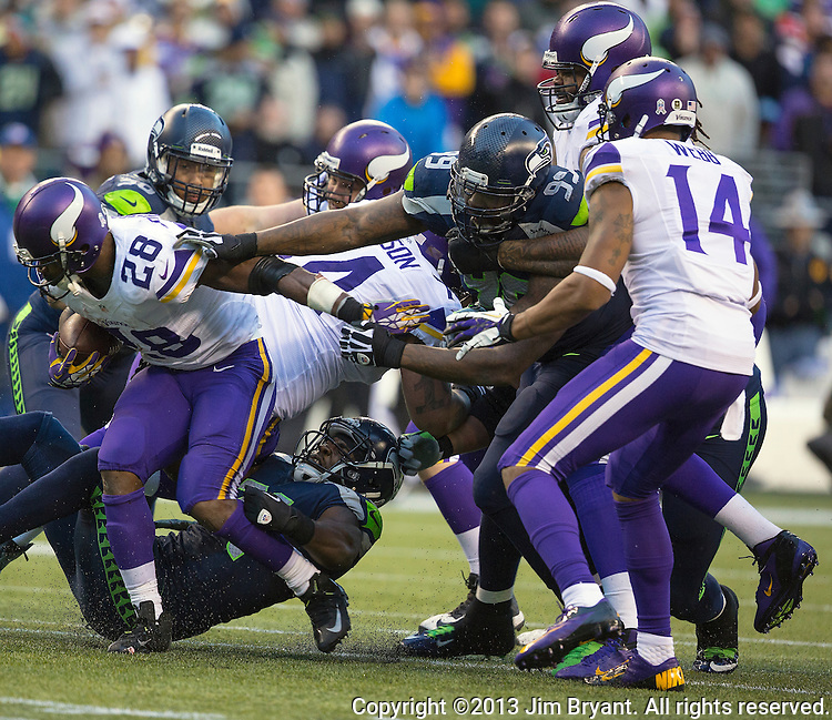 Minnesota Vikings running back Adrian Peterson (28) is tackled from behind by Seattle Seahawks Kam Chancellor, (31) and Tony McDaniel (99) at CenturyLink Field in Seattle, Washington on  November 17, 2013.  The Seahawks beat the Vikings 41-20.  ©2013.  Jim Bryant. All Rights Reserved.
