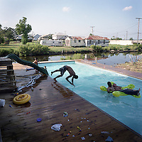 A swimming pool in Pointe Aux Chene, Louisiana replaces swimming in the bayou beside the house. Local waterways have become too polluted with rubbish and other contamination so many families maintain swimming pools instead for relief from extreme summer heat.