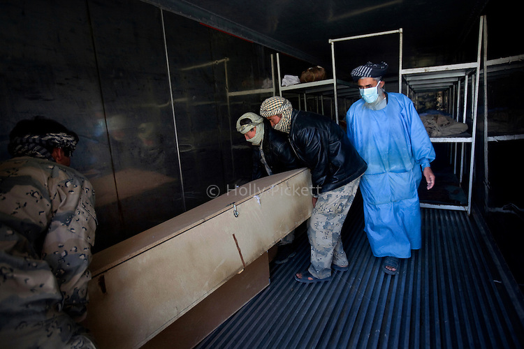 Afghan border policemen Attullah, Amanadin and Imam Gul place the coffins of their two fellow border police in the refrigerated container at the Mirwais Hospital morgue in Kandahar, Afghanistan, April 23, 2009. The day before, Ahmad Shei, 25, and Hamidullah, 22, were in an unarmored truck carrying material to a checkpoint in Zabul Province when their vehicle was hit by a roadside bomb. Four other border policemen were injured and taken to Kandahar Air Field to receive medical treatment. The two dead were to the morgue at Mirwais Hosptal before being transported to their home provinces in the North for burial. Despite worsening security, development continues at Mirwais Hosptial, where the International Committe of the Red Cross conducts training and assists the local staff. Mirwais is the main public hosptial serving five southern provinces. As security has deteriorated in the South, many international NGO's have pulled their staff from the area or shut down the regional office, stunting development in a region where it is badly needed.
