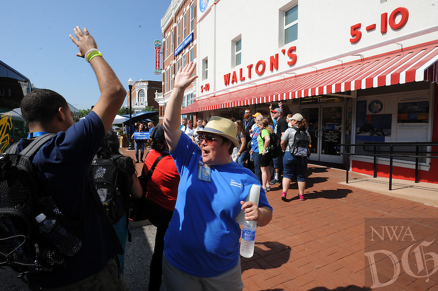 NWA Democrat-Gazette/ANDY SHUPE<br /> Jennifer Cozens, community outreach manager at the Walmart Museum, greets Sam's Club associates Wednesday, June 3, 2015, on the Bentonville square. Associates in town for the annual shareholders meeting spent time at the museum.