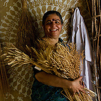 Dr. Vandana Shiva holds a bouquet of dried wheat, millet and fenugreek as she poses amongst hanging dried crops and her laboratory coat in the Navdanya Seed bank in Dehradun, Uttarakhand, India, on 6th September 2009. The inside walls of the seed bank have all been painted by Gujarati and Rajasthani tribal artists...Dr. Vandana Shiva, the founder of Navdanya Foundation and Bijavidyapeeth, is a physicist turned environmentalist who campaigns against genetically modified food and teaches farmers to rely on indigenous farming methods.. .Photo by Suzanne Lee / For The National