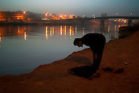 Baghdad, Iraq, March 06, 2003.Sabah, a fisherman, prays on the Tigris river bank after sunset, next to the Shuhada (martyrs) bridge.