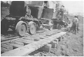 New Mexico Lumber Co. rail motorcar delivering a load of earth to track workers attempting to stabilize a soft section.<br /> New Mexico Lumber Co.  San Juan National Forest, CO  Taken by Long, Morris - ca. 1928