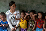 Teacher Lodema Dela Cruz Doroteo talks with children in class in Santa Ines, an indigenous village in the Philippines. A graduate of Harris Memorial College, where she benefited from a scholarship from United Methodist Women, she is the first indigenous school teacher in her village.