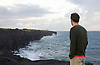 A visitor to Hawaii Volcanoes National Park on the Big Island of Hawaii, looks out over the Pacific ocean coastline. Photo by Kevin J. Miyazaki/Redux