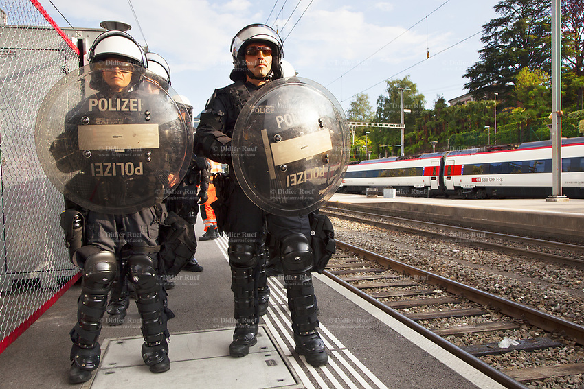 Switzerland. Canton Ticino. Lugano. Railway station. A group of police officers from TPO (Transport Police). The policemen and a policewoman wear the special riot police black uniforms and helmets. The first two hold in their hands shields. They stand on the platform and wait for the arrival of a chartered train with the FC Luzern football club's supporters. TPO (Transport Police) is the Swiss Federal Railways Police. Swiss Federal Railways (German: Schweizerische Bundesbahnen (SBB), French: Chemins de fer fédéraux suisses (CFF), Italian: Ferrovie federali svizzere (FFS)) is the national railway company of Switzerland. It is usually referred to by the initials of its German, French and Italian names, as SBB CFF FFS. 2.06.2017 © 2017 Didier Ruef