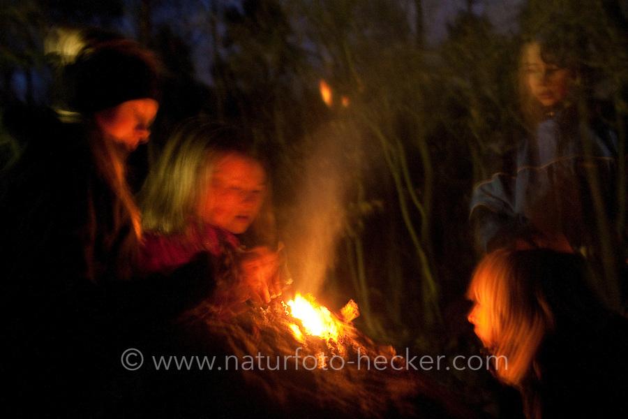 Kinder bei einem abendlichen, stimmungsvollen Lagerfeuer, Feuer